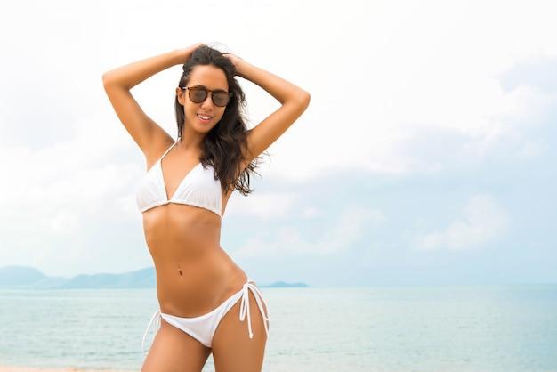 Junge schöne asiatin im weißen biniki am strand im sommer