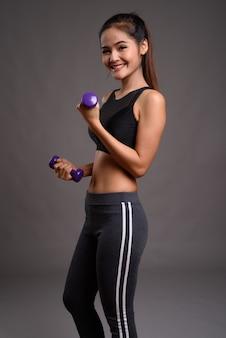 Junge schöne asiatische fitnessfrau, die hanteln hält