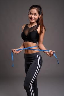 Junge schöne asiatische fitnessfrau mit schlanker taille, die maßband hält