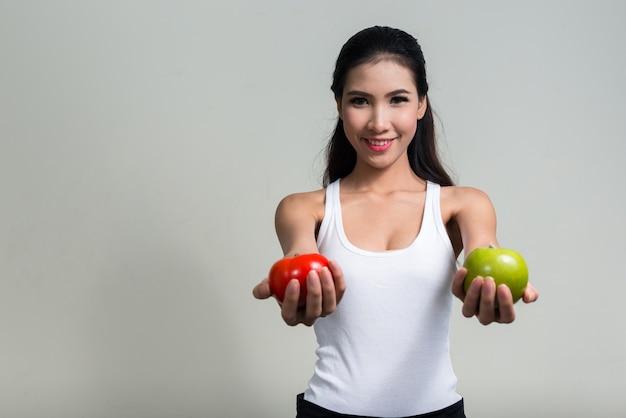 Junge schöne asiatische frau bereit für fitnessstudio gegen leerraum