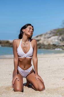 Junge schöne asiatische frau des porträts in einem weißen bikini lächelnd und in einer glücklichen strandsee- und -ozeanfreizeitreise in den feiertagsferien