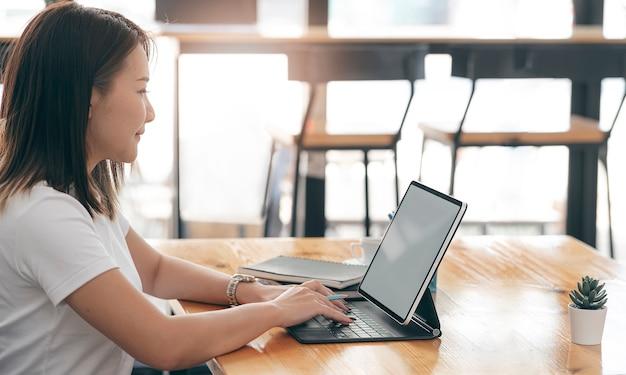 Junge schöne asiatische frau, die auf tablet-computer beim sitzen am co-arbeitsbereich arbeitet.
