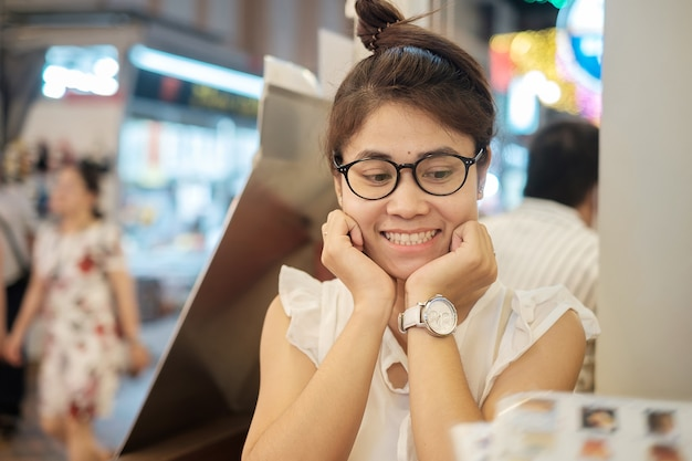 Junge schöne asiatische frau, die beim schauen der menüabendessenzeit im restaurant oder in der kaffeestube lächelt