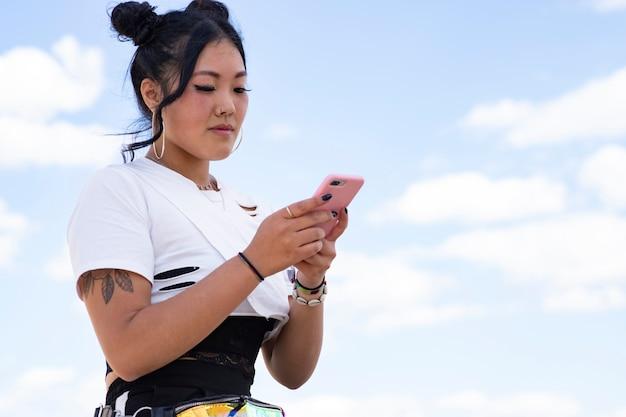 Junge schöne asiatische frau, die chirurgische maske für gesichtsschutz unter verwendung eines smartphones im park trägt