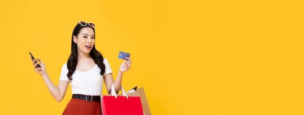 Junge schöne asiatische frau, die eine online-zahlung durch handy mit kreditkarte macht, während einkaufstaschen in der isolierten gelben fahnenwand mit kopienraum tragen