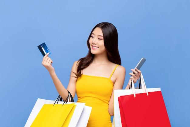 Junge schöne asiatische frau, die eine online-zahlung mit kreditkarte macht