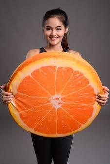 Junge schöne asiatische frau, die große orange hält