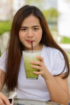 Junge schöne asiatische frau, die grünen eistee am kaffeehaus draußen trinkt