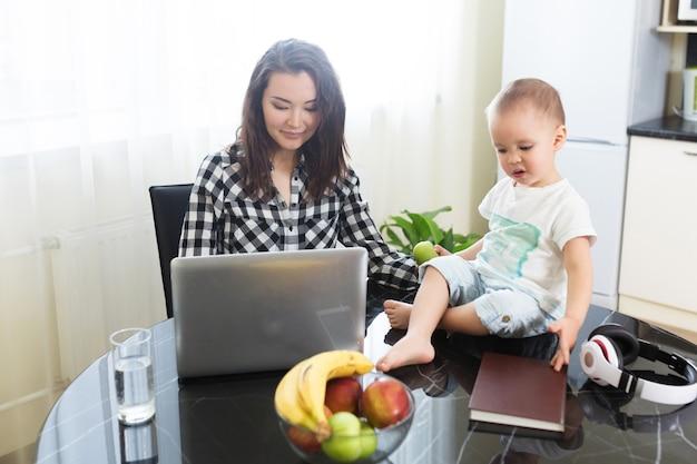 Junge schöne asiatische frau, die ihr baby anschaut, während sie am laptop arbeitet, online-geschäft von zu hause aus
