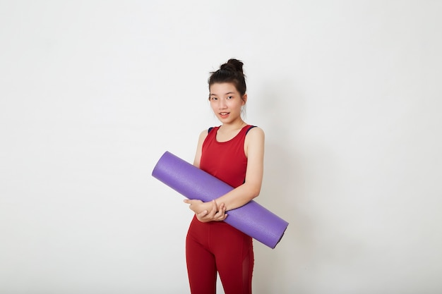 Junge schöne asiatische frau, die lila yogamatte steht und hält und bereit ist, im fitnessstudio zu trainieren, stilvolle sportbekleidung tragend.