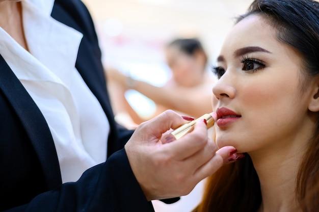 Junge schöne asiatische frau, die make-up anwendet