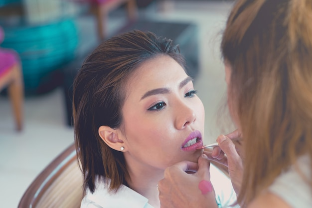 Junge schöne asiatische frau, die make-up durch make-upkünstler anwendet