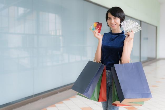 Junge schöne asiatische frau, die mit kreditkarte und geld einkauft und farbe volle einkaufstaschen in ihren armen mit lächelndem gesicht hält.
