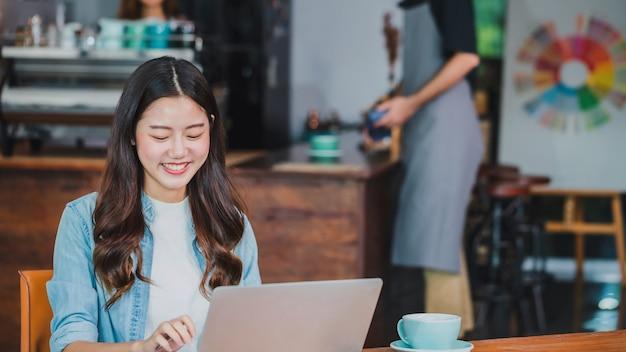 Junge schöne asiatische frau, die mit laptop in der kaffeestube arbeitet.