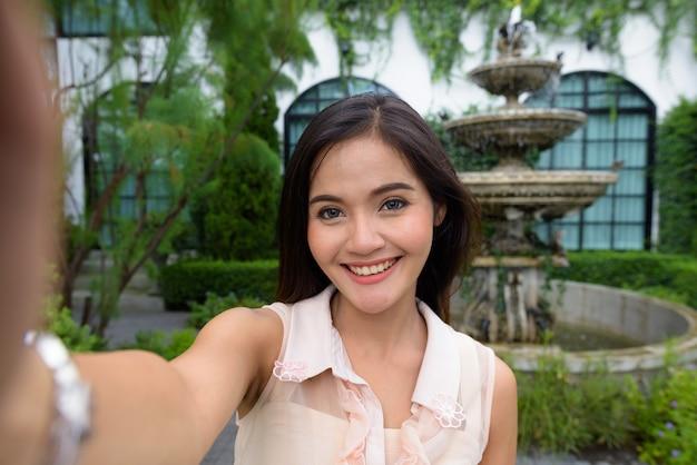 Junge schöne asiatische frau, die selfie beim entspannen nimmt