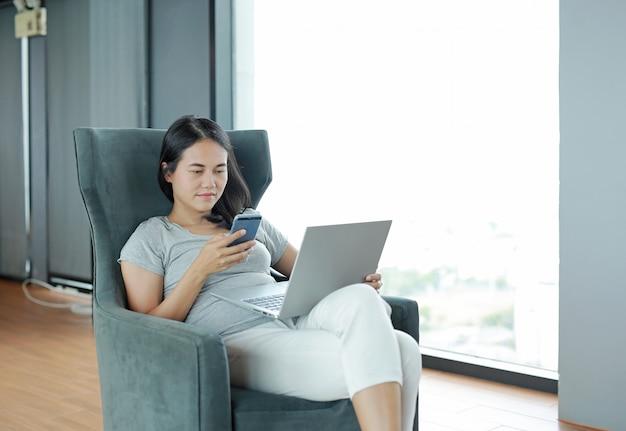 Junge schöne asiatische frau, die smartphone und laptop-computer verwendet, die online zu hause arbeiten und sich auf sessel entspannend fühlen. menschen während der introvertierten zeit zu hause von der epidemie in thailand.