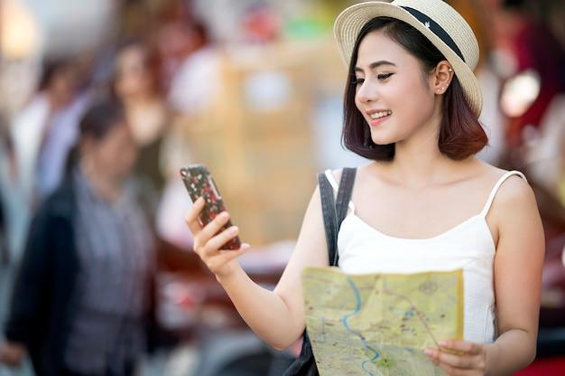 Junge schöne asiatische frau, die smartphoneschirm betrachtet und karte in ihrer hand hält