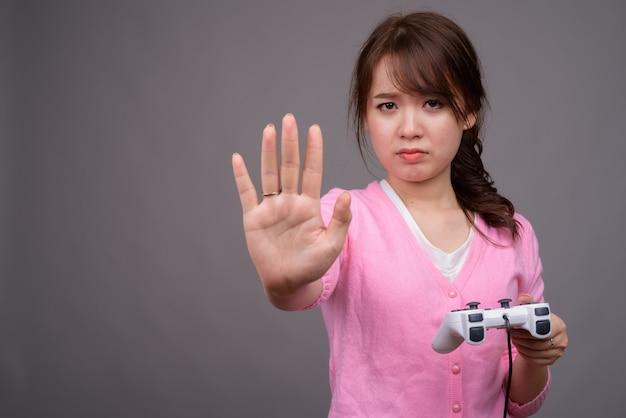 Junge schöne asiatische frau, die spiele mit gamecontroller spielt