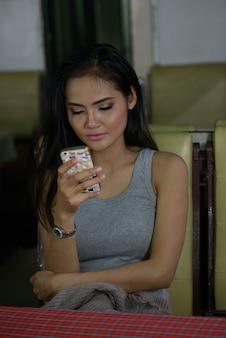 Junge schöne asiatische frau, die telefon am kaffeehaus benutzt