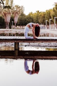 Junge schöne asiatische frau, die yoga in einem park tut. sitzen auf der brücke mit reflexion auf dem wassersee. yoga und gesundes lebensstilkonzept