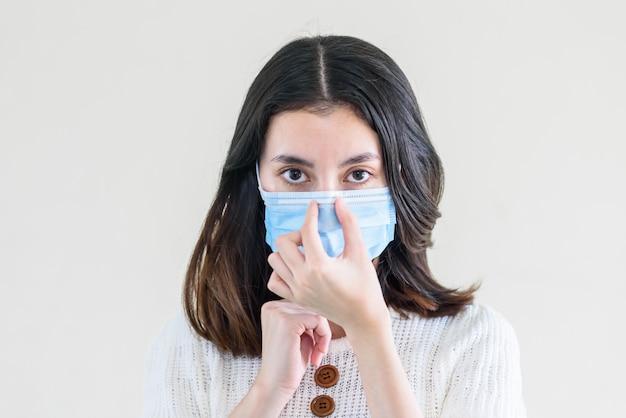 Junge schöne asiatische frau, die zeigt, wie man eine medizinische maske trägt