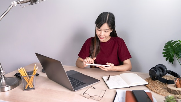 Junge schöne asiatische frau, die zu hause arbeitet