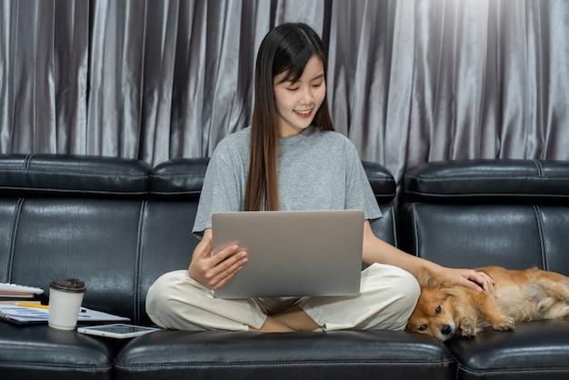 Junge schöne asiatische frau, die zu hause mit ihrem haustier arbeitet