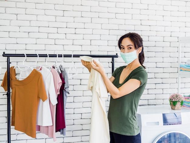Junge schöne asiatische frau, hausfrau, die lässiges tuch und schutzgesichtsmaske hält hemd hält und schmutzigen fleck auf ihm nach dem waschen prüft