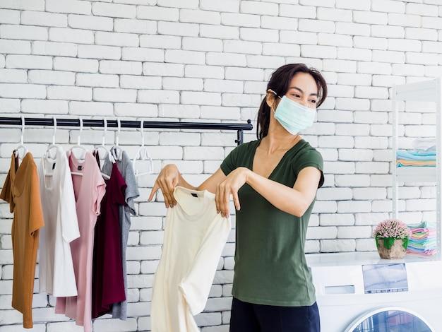 Junge schöne asiatische frau, hausfrau, die schützendes gesichtsmaskenschütteln und trocknenhemd nach dem waschen nahe waschmaschine trägt