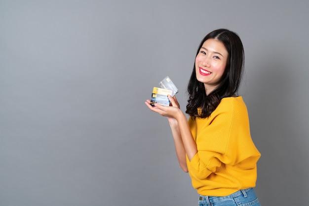 Junge schöne asiatische frau lächelt und präsentiert kreditkarte in der hand, die vertrauen und zuversicht für die zahlung auf grau zeigend zeigt