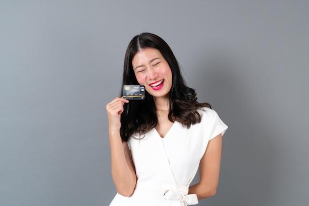Junge schöne asiatische frau mit glücklichem gesicht und präsentationskreditkarte in der hand