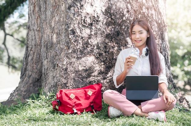 Junge schöne asiatische frau mit kopfhörer, die tasse hält, lächelt und die kamera anschaut, während sie unter dem großen baum im park mit sonnenlicht sitzt.