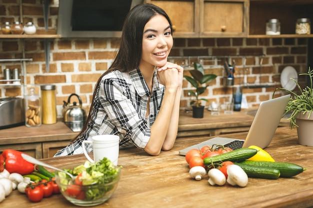Junge schöne asiatische frau mit laptop auf küche, die rezepte findet und lächelt. nahansicht.