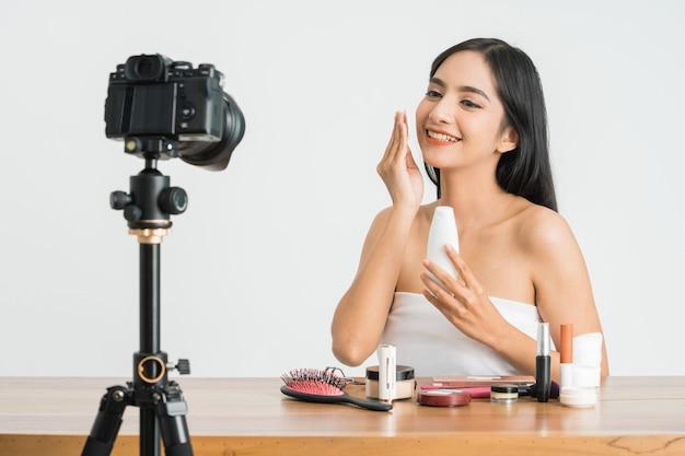 Junge schöne asiatische frau professionelle schönheit vlogger oder blogger aufnahme make-up tutorial auf social media über weiße wand zu teilen