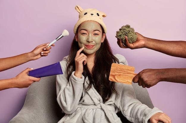 Junge schöne asiatische frau trägt feuchtigkeitsspendende gesichtsmaske, bequem gekleidet