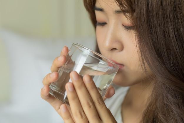 Junge schöne asiatische frauen, die frisches glas wasser trinken. gesundheitskonzept.