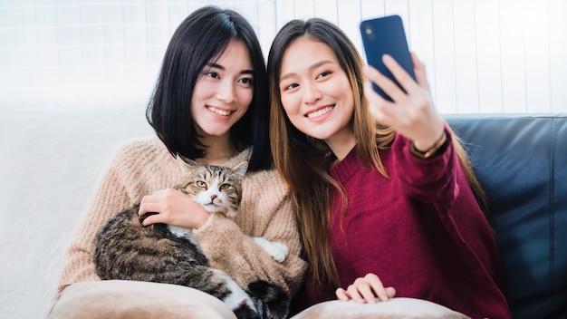 Junge schöne asiatische frauen lesbenpaar liebhaber mit smartphone selfie niedlichen katze haustier im wohnzimmer zu hause mit lächelndem gesicht. konzept der lgbt-sexualität mit glücklichem lebensstil zusammen.