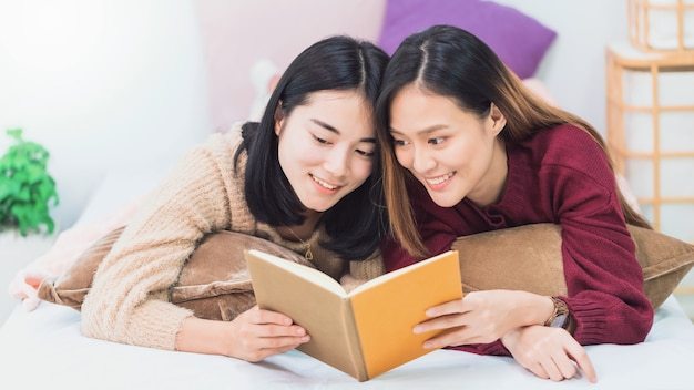 Junge schöne asiatische frauen lesbisches paar liebhaber lesebuch im wohnzimmer zu hause.