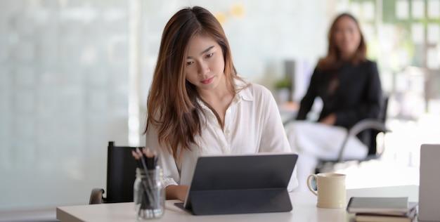 Junge schöne asiatische geschäftsfrau, die an ihrem projekt mit tablette arbeitet