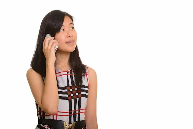 Junge schöne asiatische geschäftsfrau, die auf handy lokalisiert spricht