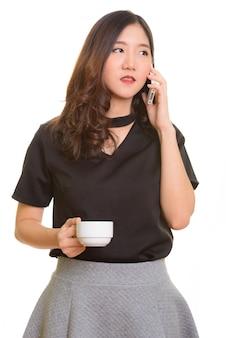 Junge schöne asiatische geschäftsfrau, die auf handy spricht, während kaffeetasse hält
