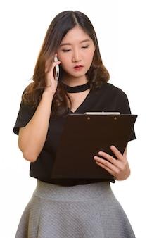 Junge schöne asiatische geschäftsfrau, die auf handy spricht, während zwischenablage liest