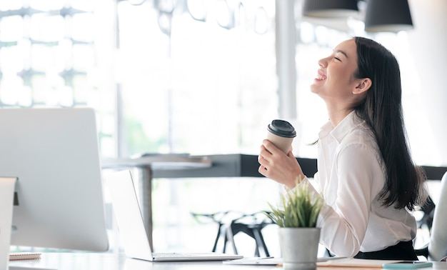 Junge schöne asiatische geschäftsfrau, die tasse kaffee hält und während der arbeit im büro lächelt.