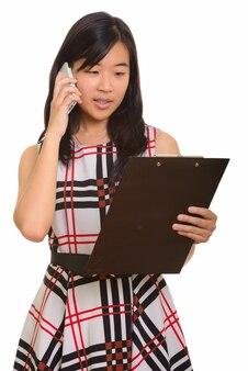 Junge schöne asiatische geschäftsfrau, die zwischenablage liest, während auf handy spricht