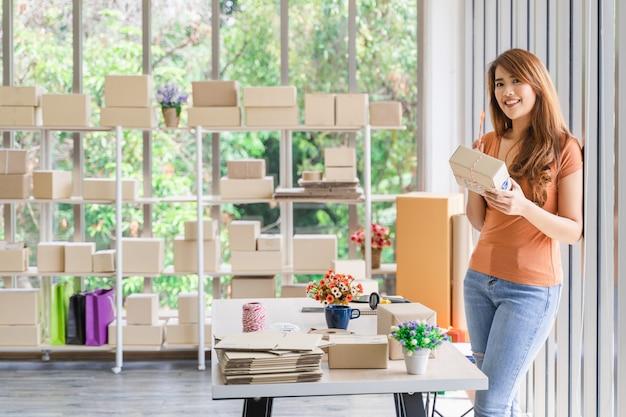 Junge schöne asiatische geschäftsfrau mit smiley hält einen paketkasten