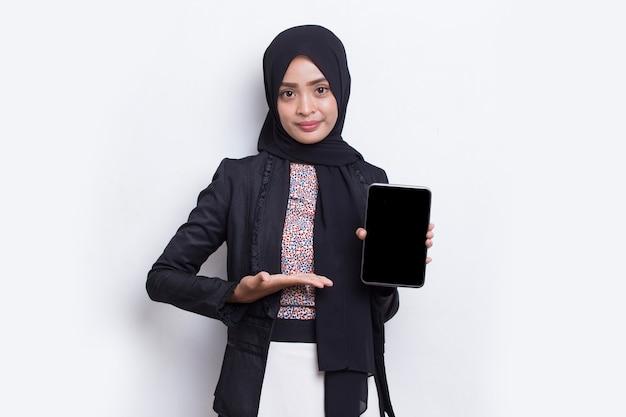 Junge schöne asiatische muslimische frau demonstriert handy isoliert auf weißem hintergrund