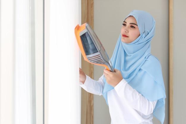 Junge schöne asiatische muslimische frau, die weißen vorhang mit staubsauger im wohnzimmer reinigt