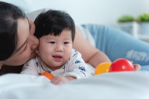Junge schöne asiatische mutter mit asiatischem baby auf bett