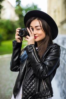 Junge schöne asiatische reisende frau, die digitale kompaktkamera und lächeln verwendet und kopierraum betrachtet. reise reise lebensstil, weltreiseforscher. asien-sommertourismus-konzept