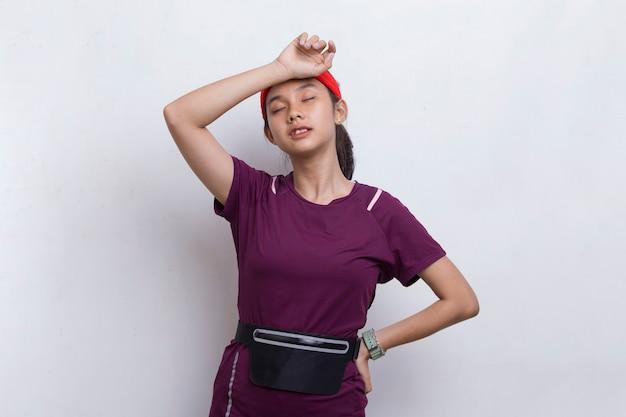 Junge schöne asiatische sportfrau, die sich nach dem training auf weißem hintergrund müde fühlt